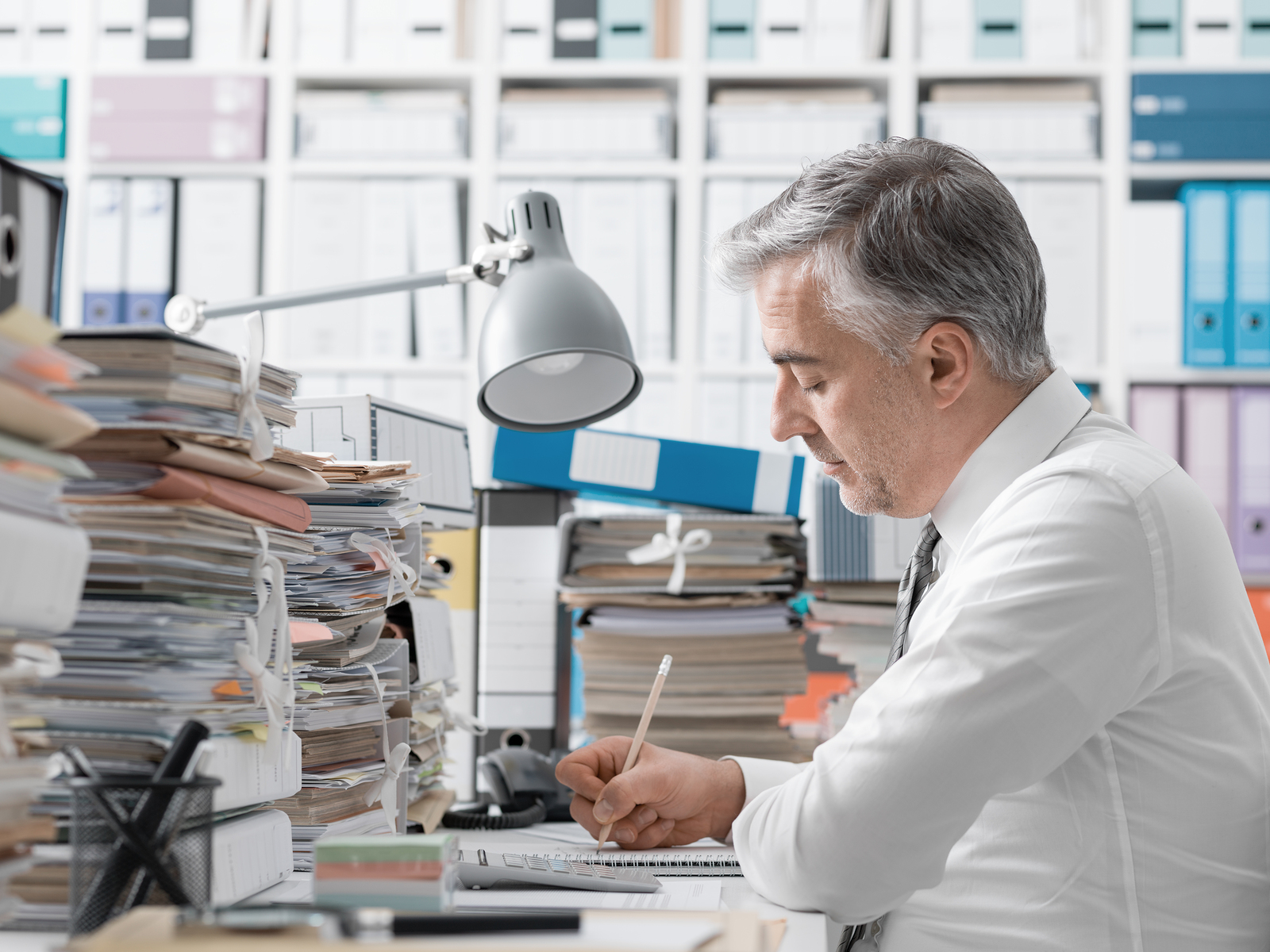 Desperate businessman working in the office late at night and overloaded with work, his desktop is covered with paperwork: business management and deadlines concept